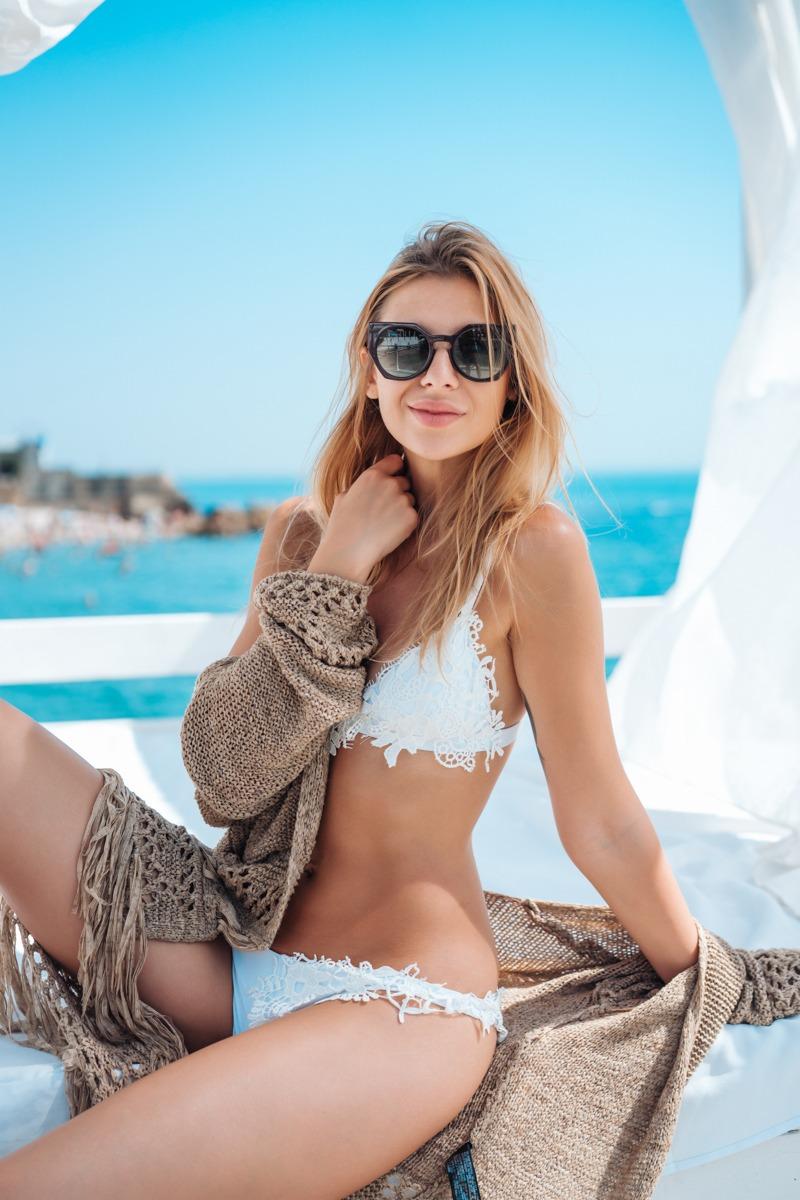 beautiful woman in a white bikini by the sea on a beach bed