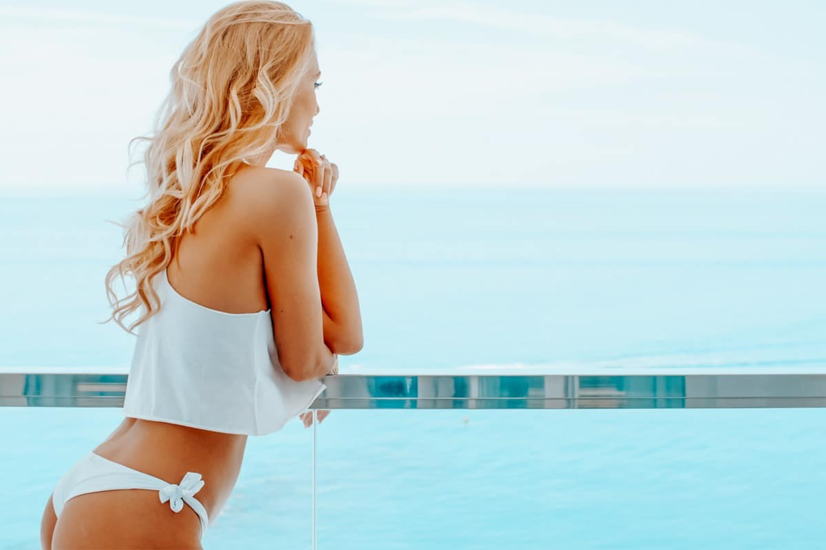 Blond attractive woman wearing white bikini and silky sleeveless top while leaning on the balcony of a hotel room with wide ocean view  side rear