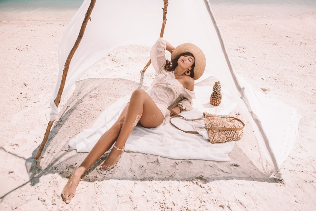 Travel vacation, summer pleasure concept. Attractive brunette woman laying on a deserted beach under the handmade tent. Perfect slim mixed race Asian Caucasian woman with perfect long legs wearing a white dress, hat, ornamentation. Fashionable trendy boho style. Tanned beautiful model in bohemian chic clothing resting with closed eyes on the shore in sunny day.