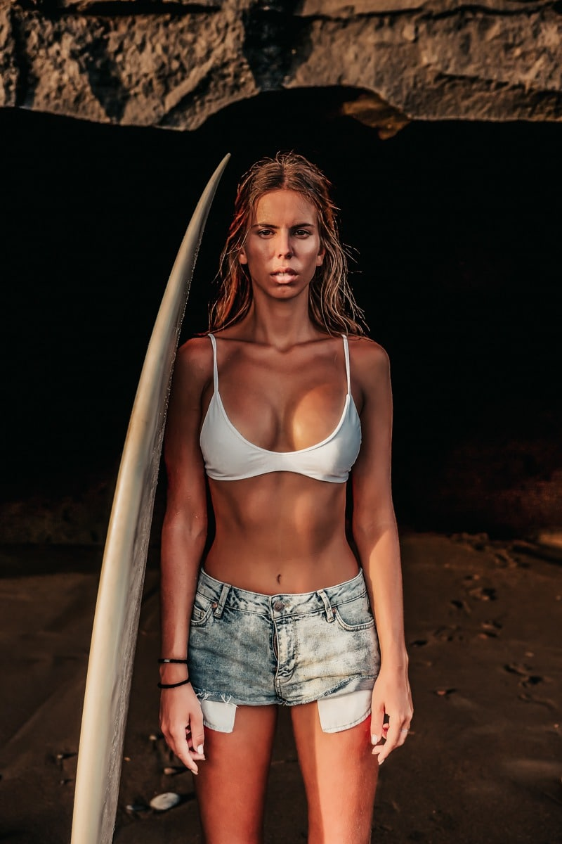 Young surfer pretty woman in sexy white bikini and short denim shorts with white surfing shortboard pose in cave at beach. People water sport adventure camp and extreme swim on summer vacation