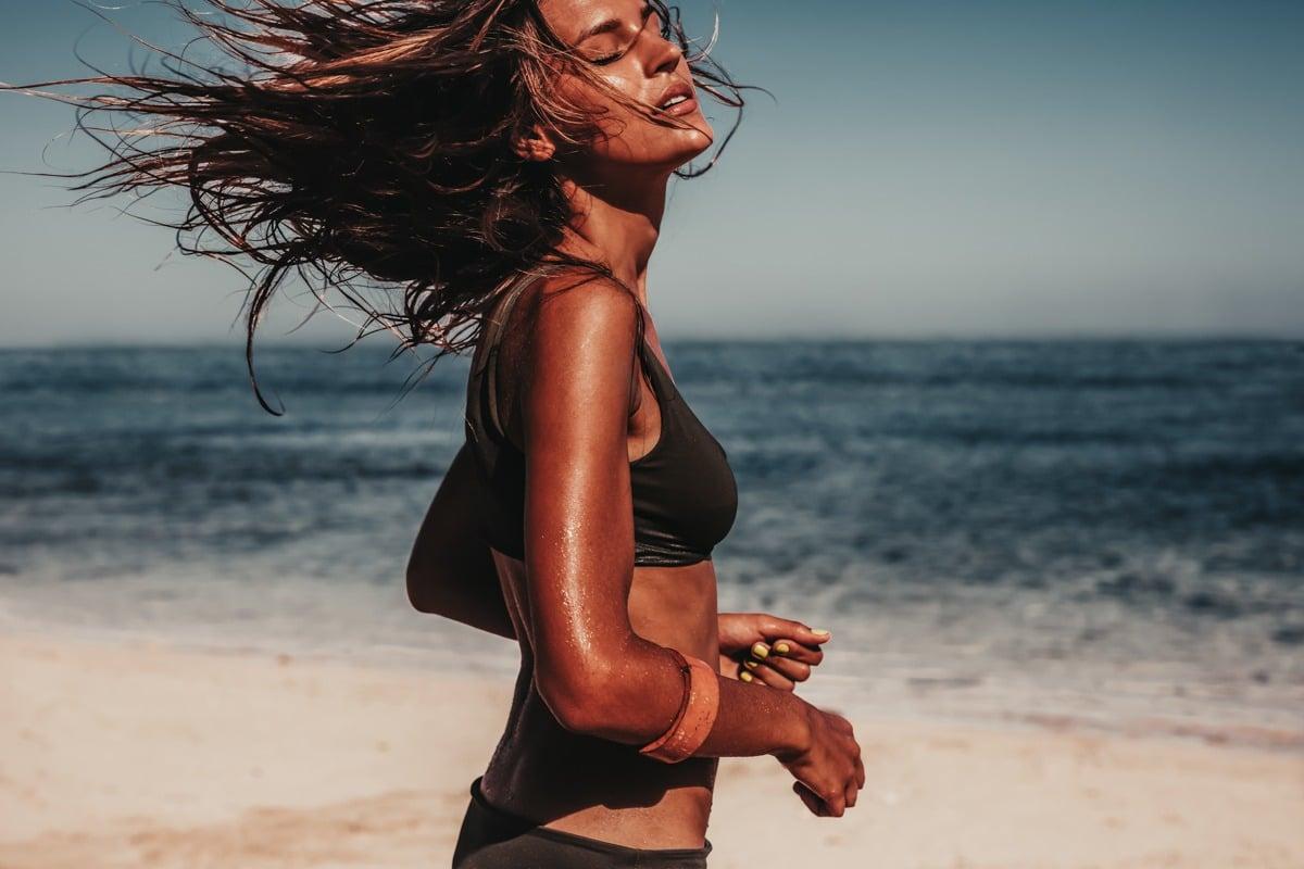 Shot of young woman in bikini running on the beach. Caucasian female model on the sea shore.