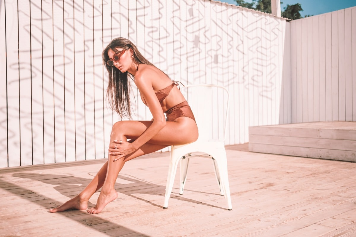 Beautiful sexy brunette girl in swimsuit and sunglasses thoughtfully smearing body with sunscreen cream sunbathing on chair on beach